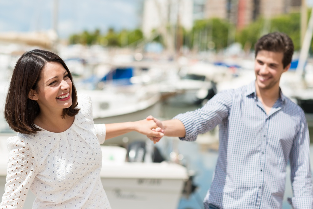 Attractive couple exploring on their summer vacation laughing as they hold hands while sightseeing a small boat harbour on the coast