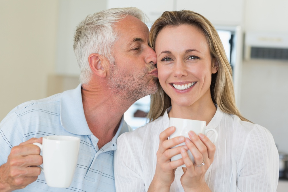 Casual man giving his smiling partner a kiss on the cheek at home in the kitchen.jpeg